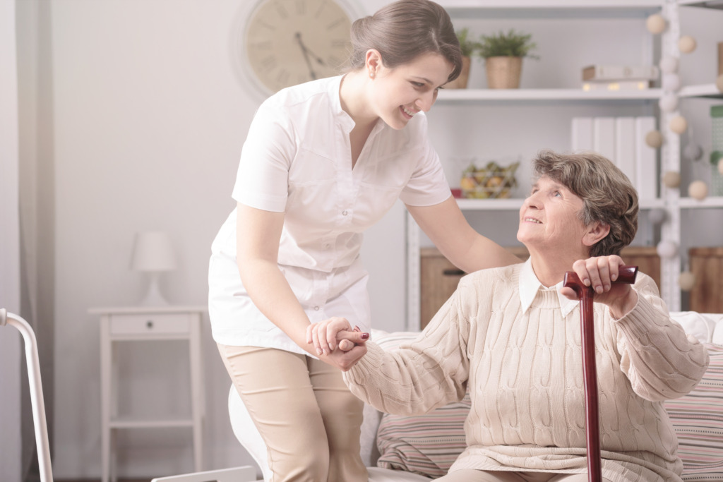 Young nurse supporting senior disabled woman with walking stick in a retirement home